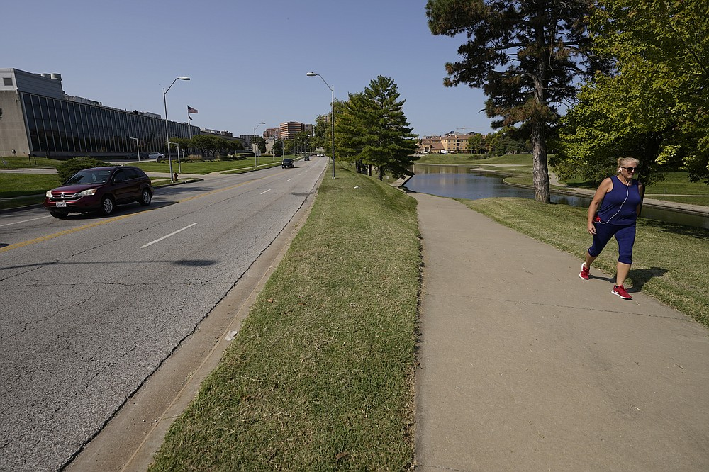 A woman walks on a trail adjacent to Volker Road Thursday, Sept. 24, 2020, in Kansas City, Mo. The stretch of road, along with parts of two other streets, would be renamed to honor Rev. Martin Luther King Jr. under a city proposal coming in the wake of failed effort to honor King last year. (AP Photo/Charlie Riedel)