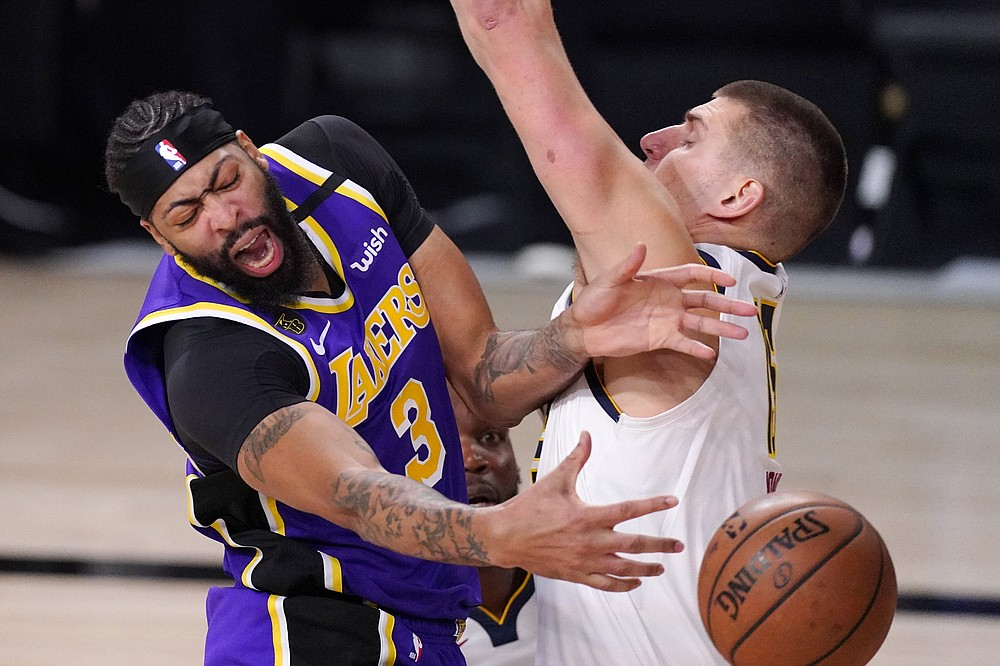Los Angeles Lakers' Anthony Davis (3) passes the ball around Denver Nuggets' Nikola Jokic (15) during the second half of an NBA conference final playoff basketball game Saturday, Sept. 26, 2020, in Lake Buena Vista, Fla. (AP Photo/Mark J. Terrill)