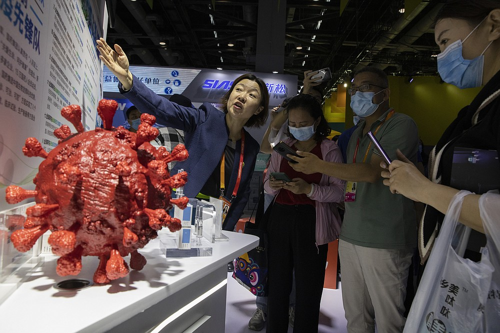 An employee answers questions from the public near samples of a COVID-19 vaccine produced by Sinopharm subsidiary CNBG are displayed during a trade fair in Beijing on Sept. 6, 2020. State-backed Sinopharm's subsidiary CNBG has injected 350,000 people outside its clinical trials for COVID-19 vaccine, which have about 40,000 people enrolled. It's a highly unusual move that raises ethical and safety questions, as companies and governments worldwide race to develop a vaccine that will stop the spread of the new coronavirus. (AP Photo/Ng Han Guan)