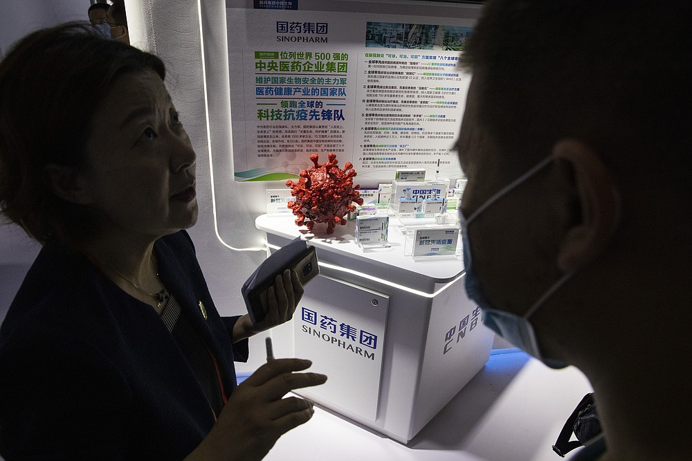 An employee answers questions from the public near samples of a COVID-19 vaccine produced by Sinopharm subsidiary CNBG are displayed during a trade fair in Beijing on Sept. 6, 2020. CNBG has injected 350,000 people outside its clinical trials for COVID-19 vaccine, which have about 40,000 people enrolled. It's a highly unusual move that raises ethical and safety questions, as companies and governments worldwide race to develop a vaccine that will stop the spread of the new coronavirus. (AP Photo/Ng Han Guan)