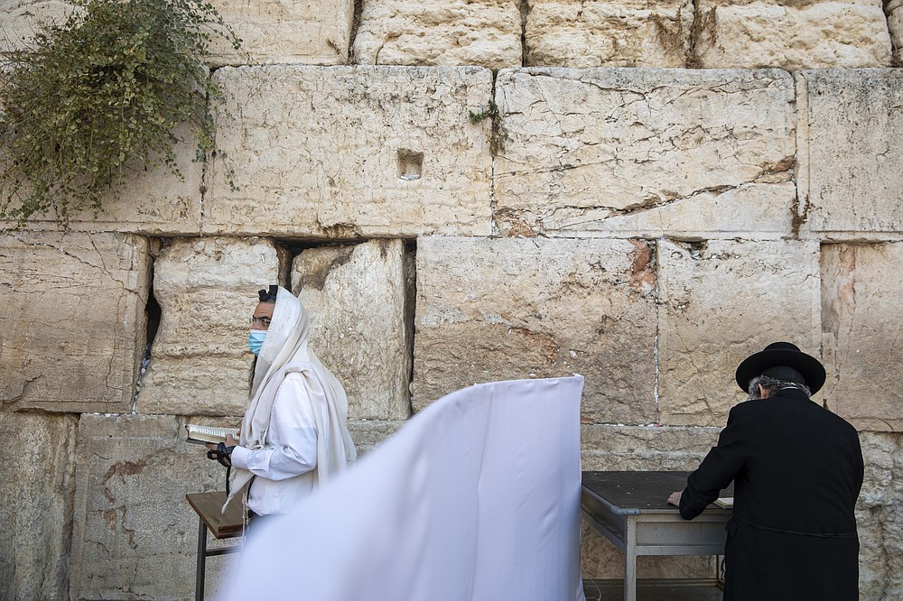 With social distancing barrier, ultra-Orthodox Jewish men pray ahead of Yom Kippur, the holiest day in the Jewish year, at the Western Wall, the holiest site where Jews can pray in Jerusalem's Old City, Sunday, Sept. 27, 2020. For Israel's ultra-Orthodox Jews, coronavirus restrictions have raised numerous questions about how to maintain their religious lifestyle during the outbreak. A religious publisher in Jerusalem released a book in July with over 600 pages of guidance from 46 different rabbis. (AP Photo/Ariel Schalit)