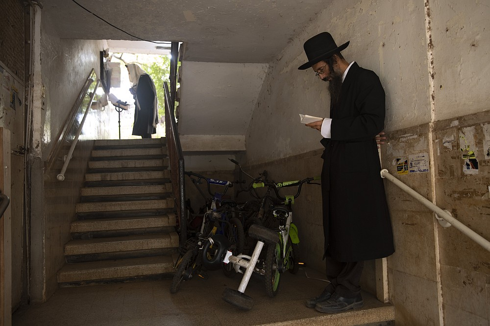 Ultra-Orthodox Jews keep social distancing and wear face masks during a morning prayer next to their houses as synagogues are limited to twenty people due to the coronavirus pandemic, in Bnei Brak, Israel, Thursday, Sept 24, 2020. For Israel's ultra-Orthodox Jews, coronavirus restrictions have raised numerous questions about how to maintain their religious lifestyle during the outbreak. A religious publisher in Jerusalem released a book in July with over 600 pages of guidance from 46 different rabbis. (AP Photo/Oded Balilty)