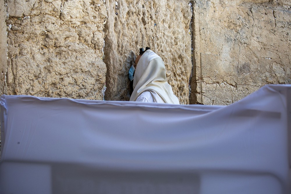 With social distancing barrier, an ultra-Orthodox Jewish man prays ahead of Yom Kippur, the holiest day in the Jewish year, at the Western Wall, in Jerusalem's Old City, Sunday, Sept. 27, 2020. For Israel's ultra-Orthodox Jews, coronavirus restrictions have raised numerous questions about how to maintain their religious lifestyle during the outbreak. A religious publisher in Jerusalem released a book in July with over 600 pages of guidance from 46 different rabbis. (AP Photo/Ariel Schalit)