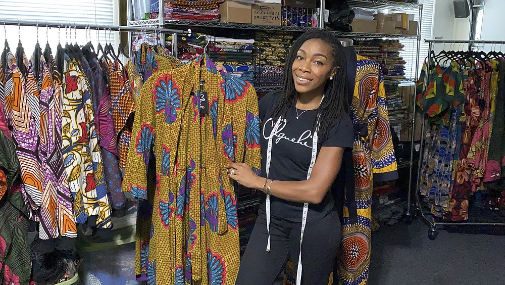 """Iguehi James, an Oakland fashion entrepreneur, shows a kimono duster she designed for her apparel company Love Iguehi, Tuesday, Sept. 15, 2020, in Oaklnad, Calif. She received a $5,000 grant from the Oakland African American Chamber of Commerce's """"Resiliency Fund,"""" which seeks to help Black-owned businesses stay afloat during the coronavirus pandemic. (AP Photo/Terry Chea)"""
