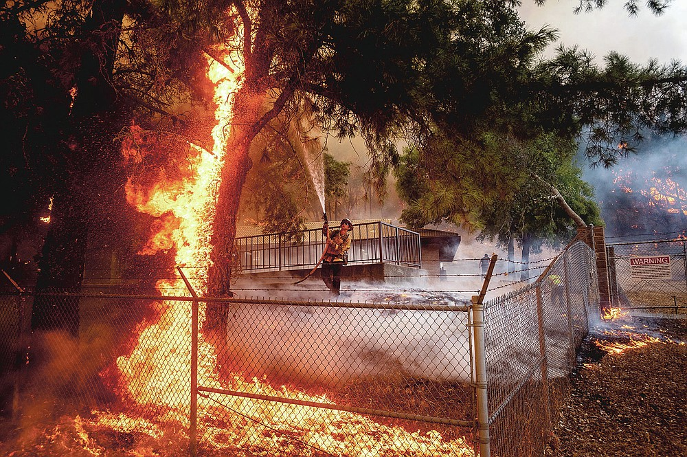 Cal Fire Capt. Jesse Campbell works to save the Louis Stralla Water Treatment Plant as the Glass Fire burns in St. Helena, Calif., on Sunday, Sept. 27, 2020. (AP Photo/Noah Berger)
