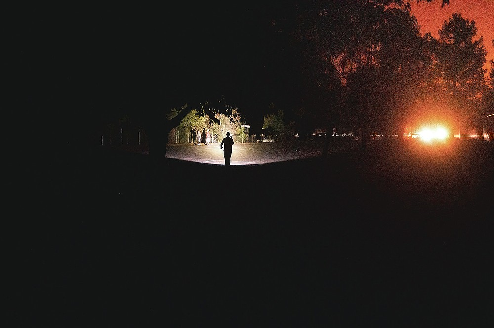 As the Shady Fire approaches, a man uses a flashlight to cross a darkened parking lot after power was cut to his area of Santa Rosa, Calif., Sunday, Sept. 27, 2020. (AP Photo/Noah Berger)