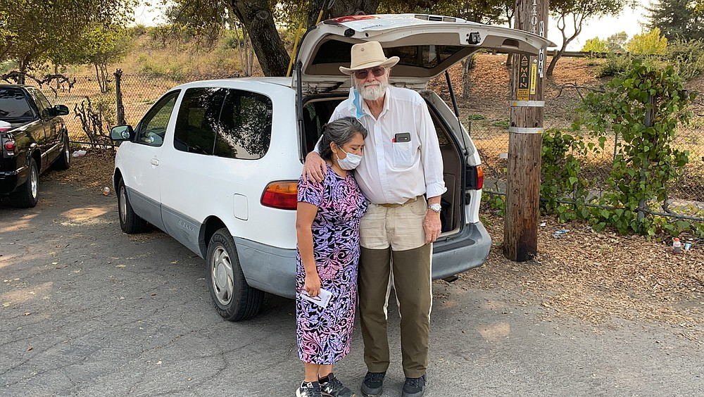 Wildfire evacuees Mike Christianson and his wife Mluz Torres stand in front their minivan outside a church shelter in Napa, Calif. on Tuesday, Sept. 29, 2020. They learned Monday their house in Deer Park in Napa Valley burned down. (AP Photo/Terry Chea)