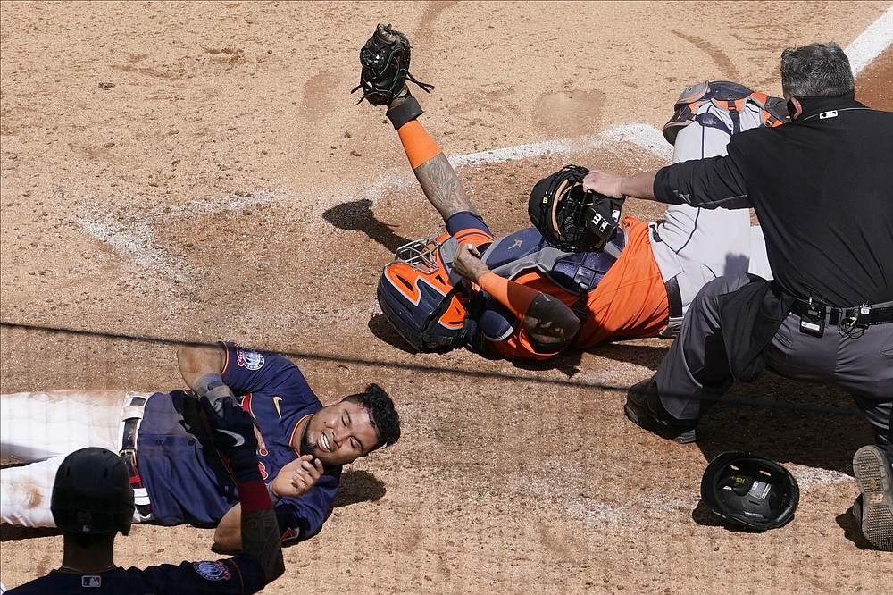 Home plate umpire Manny Gonzalez, right, makes the call after Minnesota Twins' Luis Arraez, left, is tagged out by Houston Astros catcher Martin Maldonado as he attempted to score on a Marwin Gonzalez single in the fifth inning of Game 2 of an American League wild-card baseball series, Wednesday, Sept. 30, 2020, in Minneapolis. Home plate umpire Manny Gonzalez watches to make the call.  (AP Photo/Jim Mone)