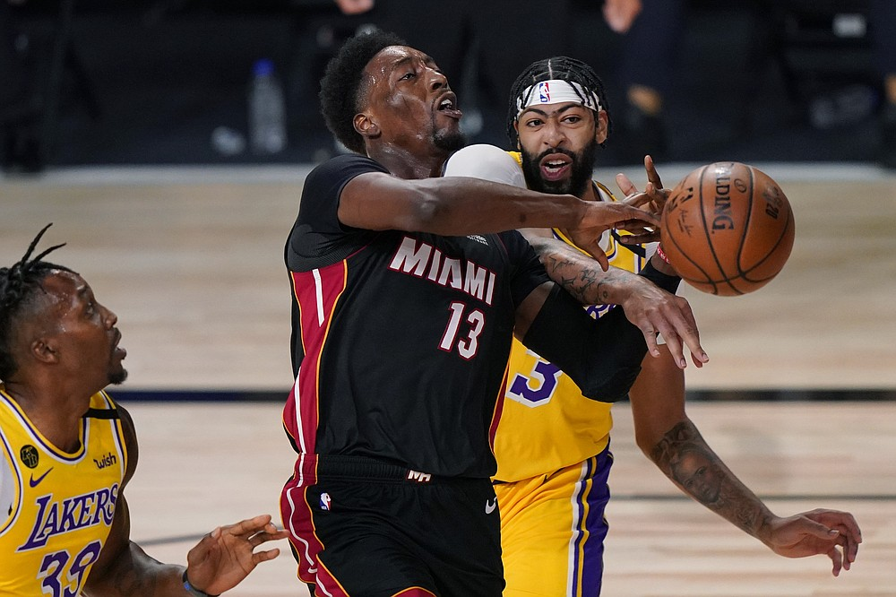 Los Angeles Lakers' Anthony Davis, right, stops Miami Heat's Bam Adebayo (13) on a drive to the basket during the first half of Game 1 of basketball's NBA Finals Wednesday, Sept. 30, 2020, in Lake Buena Vista, Fla. (AP Photo/Mark J. Terrill)