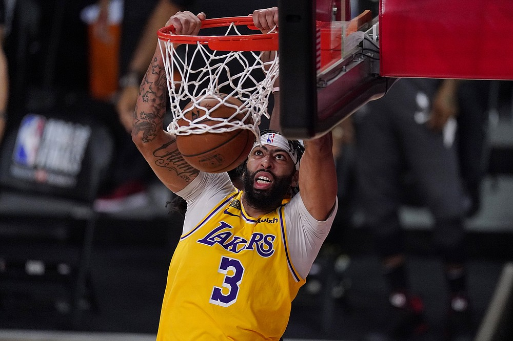 Los Angeles Lakers' Anthony Davis (3) slams a dunk against the Miami Heat during the second half of Game 1 of basketball's NBA Finals Wednesday, Sept. 30, 2020, in Lake Buena Vista, Fla. (AP Photo/Mark J. Terrill)