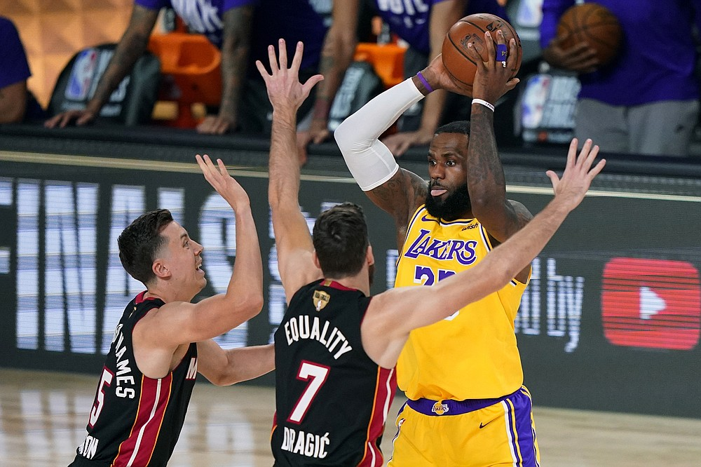Los Angeles Lakers' LeBron James, right, looks to pass while covered by Miami Heat's Duncan Robinson, left, and Goran Dragic (7) during the first half of Game 1 of basketball's NBA Finals Wednesday, Sept. 30, 2020, in Lake Buena Vista, Fla. (AP Photo/Mark J. Terrill)