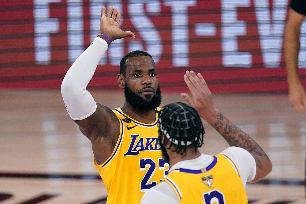 Los Angeles Lakers' LeBron James (23) high-fives Anthony Davis during the second half of Game 1 of basketball's NBA Finals Wednesday, Sept. 30, 2020, in Lake Buena Vista, Fla. (AP Photo/Mark J. Terrill)