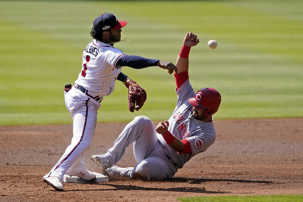 Atlanta Braves second baseman Ozzie Albies (1) throws to first after forcing out Cincinnati Reds' Eugenio Suarez (7) during the second inning in Game 2 of a National League wild-card baseball series, Thursday, Oct. 1, 2020, in Atlanta. The Reds' Mike Moustakas was safe at first. (AP Photo/John Bazemore)