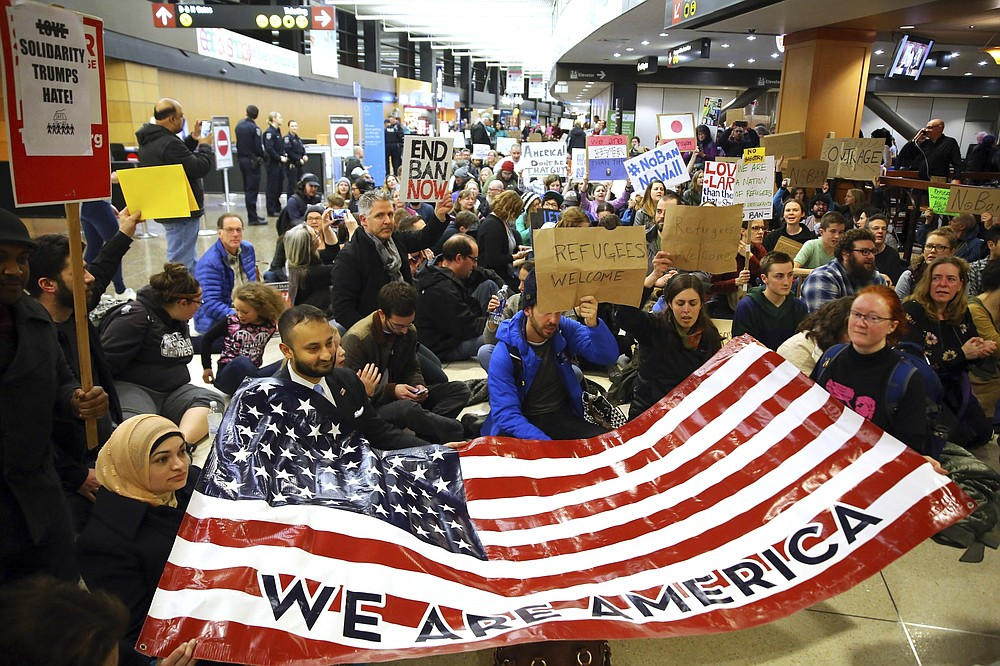 """FILE - In this Jan. 28, 2017, file photo, demonstrators sit in the concourse at Seattle-Tacoma International Airport in Seattle, Wash., with a sign that reads """"We are America,"""" as more than 1,000 people gather to protest the order signed the day before by President Donald Trump that restricts immigration to the U.S. A federal judge on Thursday, Oct. 1, 2020, temporarily lifted a visa ban on a large number of work permits, undercutting a measure that the Trump administration says will protect American jobs in a pandemic-wracked economy.  (Genna Martin/seattlepi.com via AP)"""