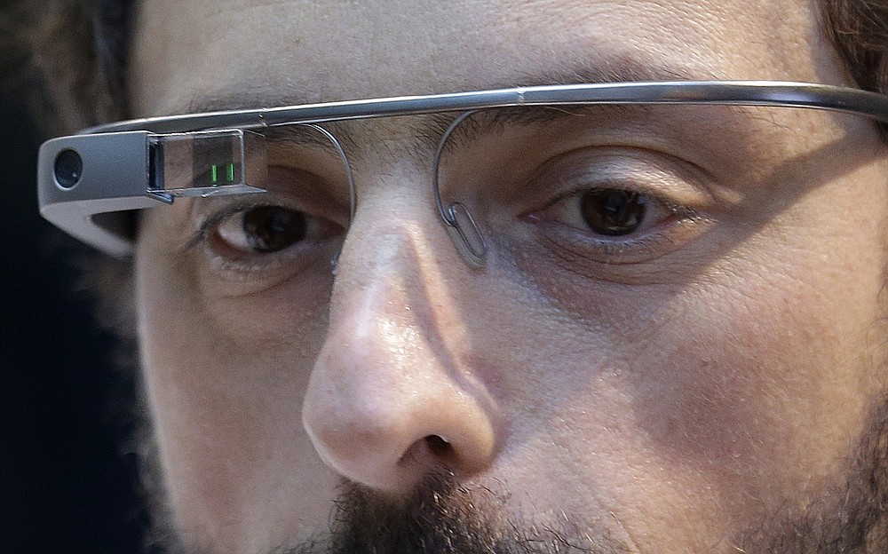 FILE - In this Feb. 20 2013 file photo, Google co-founder Sergey Brin wears a Google Glass device in San Francisco. Brin immigrated to the United States with his family from the Soviet Union at the age of six. From AT&T's Alexander Graham Bell to Brin, immigrants have long been more likely than native-born Americans to realize the dream of owning their own company. A federal judge on Thursday, Oct. 1, 2020, temporarily lifted a visa ban on a large number of work permits, undercutting a measure that the Trump administration says will protect American jobs in a pandemic-wracked economy.  (AP Photo/Jeff Chiu, File)