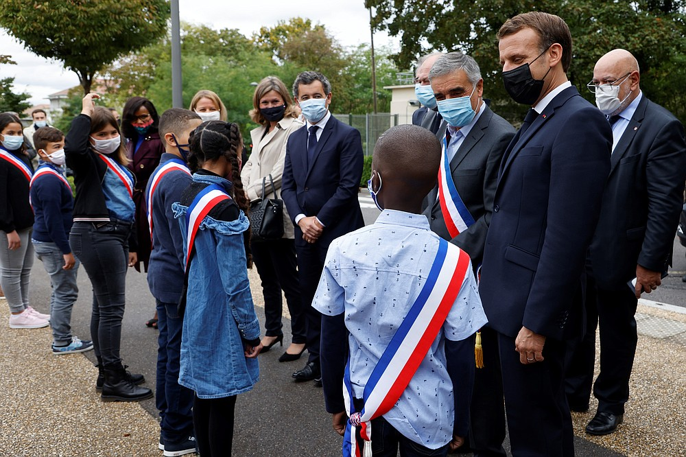 """French President Emmanuel Macron, right, wearing a protective face mask speaks to youngsters standing in line outside the 'la Maison des habitants' (MDH) in Les Mureaux, northwest of Paris, Friday, Oct. 2, 2020. President Emmanuel Macron, trying to rid France of what authorities say is a """"parallel society"""" of radical Muslims thriving outside the values of the nation, is laying the groundwork Friday for a proposed law aimed at helping remedy the phenomenon. (Ludovic Marin / Pool via AP)"""