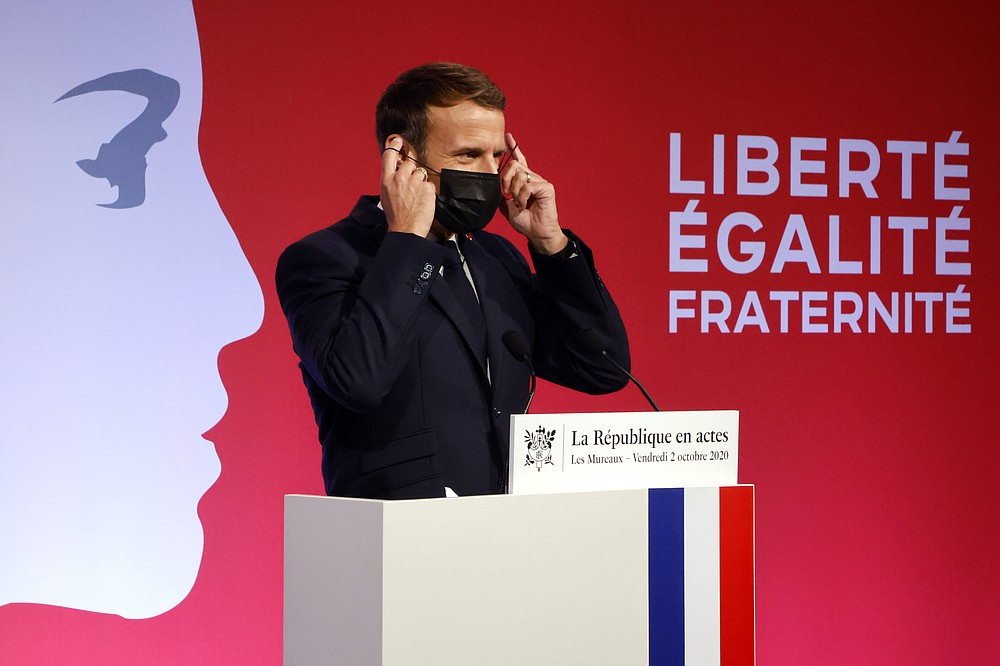"""French President Emmanuel Macron wears his mask after deliveing a speech to present his strategy to fight separatism, Friday Oct. 2, 2020 in Les Mureaux, outside Paris. President Emmanuel Macron, trying to rid France of what authorities say is a """"parallel society"""" of radical Muslims thriving outside the values of the nation, is laying the groundwork Friday for a proposed law aimed at helping remedy the phenomenon. (Ludovic Marin / POOL via AP)"""