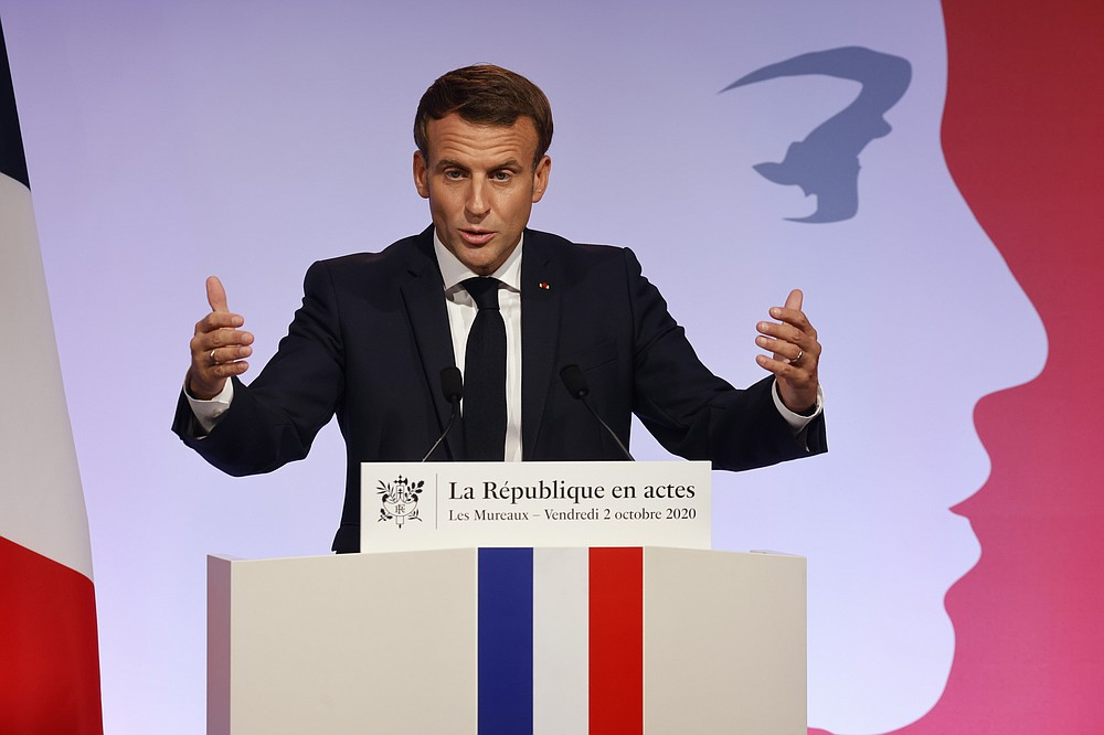 """French President Emmanuel Macron delivers a speech to present his strategy to fight separatism, Friday Oct. 2, 2020 in Les Mureaux, outside Paris. President Emmanuel Macron, trying to rid France of what authorities say is a """"parallel society"""" of radical Muslims thriving outside the values of the nation, is laying the groundwork Friday for a proposed law aimed at helping remedy the phenomenon. (Ludovic Marin / POOL via AP)"""