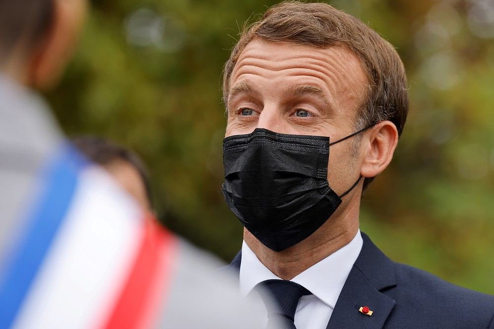 """French President Emmanuel Macron wears a protective face mask as he arrives at the 'la Maison des habitants' (MDH) in Les Mureaux, northwest of Paris, Friday, Oct. 2, 2020. President Emmanuel Macron, trying to rid France of what authorities say is a """"parallel society"""" of radical Muslims thriving outside the values of the nation, is laying the groundwork Friday for a proposed law aimed at helping remedy the phenomenon. (Ludovic Marin / Pool via AP)"""