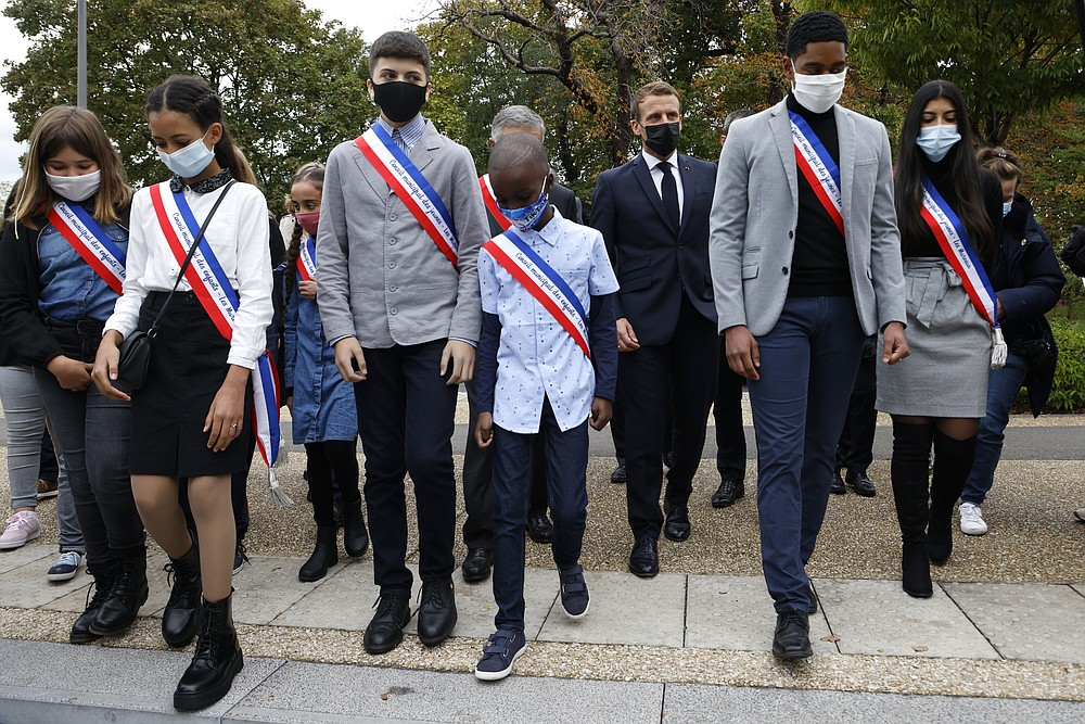 """Young representatives of the municipal council attend ceremony with French President Emmanuel Macron in Les Mureaux, northwest of Paris, Friday, Oct. 2, 2020. President Emmanuel Macron, trying to rid France of what authorities say is a """"parallel society"""" of radical Muslims thriving outside the values of the nation, is laying the groundwork Friday for a proposed law aimed at helping remedy the phenomenon. (Ludovic Marin / POOL via AP)"""