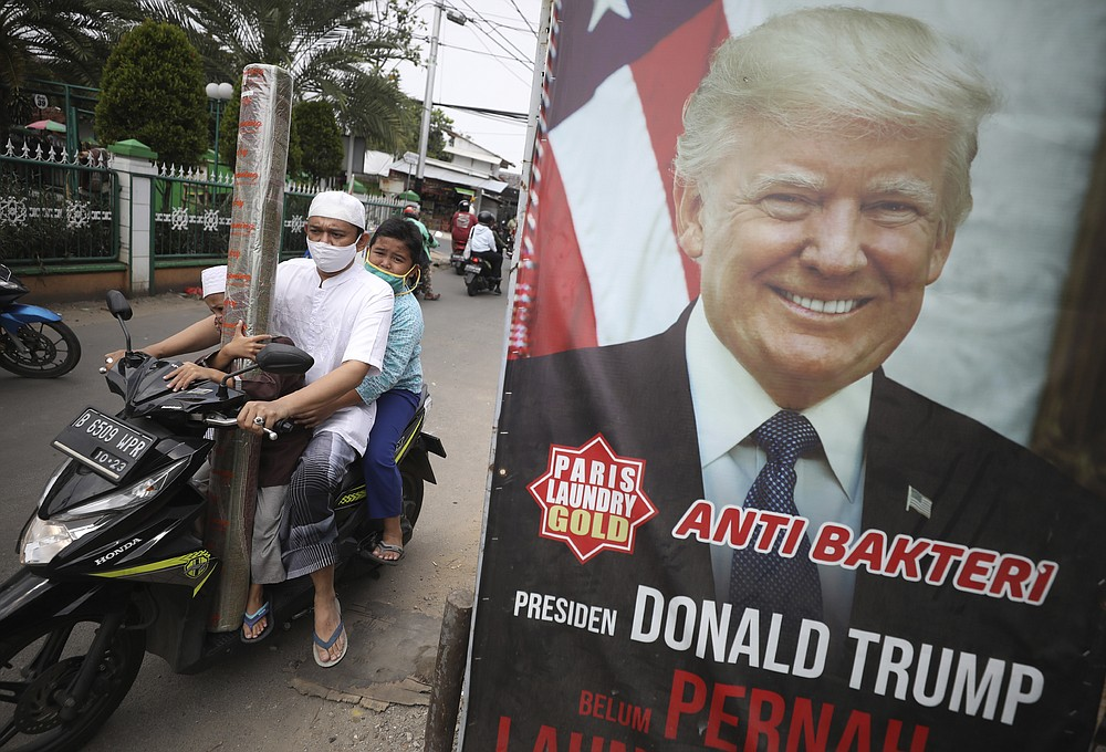 """A man and his sons wearing face masks as a precaution against the coronavirus, ride past an advertisement using a portrait of U.S. President Donald Trump as a gimmick to attract people's attention in Ciputat, Indonesia, Friday, Oct. 2, 2020. President Trump said early Friday that he and first lady Melania have tested positive for the coronavirus, a stunning announcement that plunges the country deeper into uncertainty just a month before the presidential election. Writings on the signboard read: """"Anti-bacterial"""" and """"President Donald Trump has never dropped his laundry here."""" (AP Photo/Dita Alangkara)"""