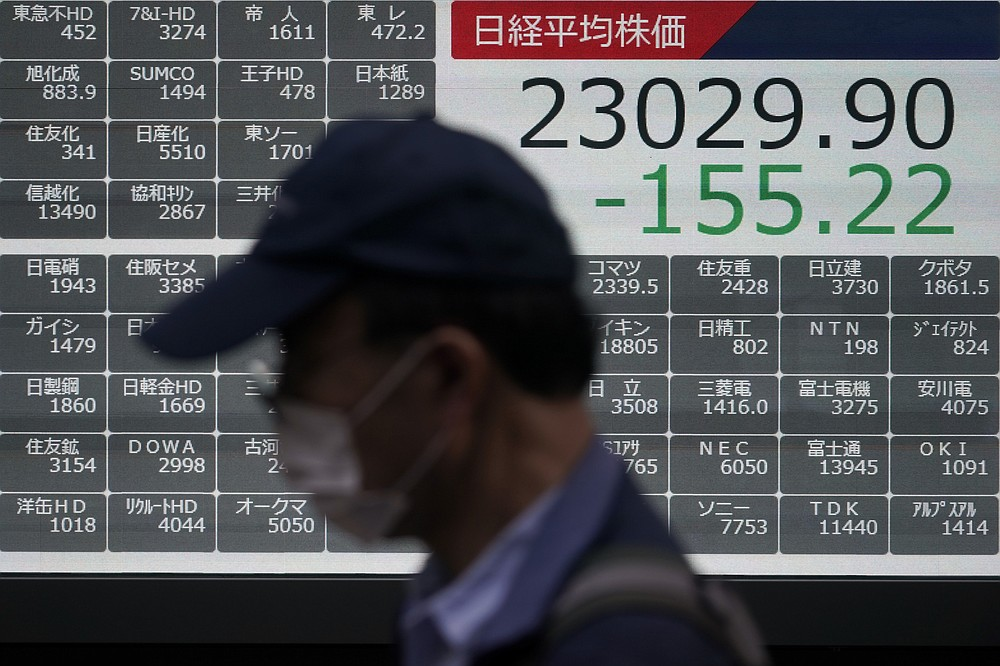 A man walks past an electronic stock board showing Japan's Nikkei 225 index at a securities firm in Tokyo Friday, Oct. 2, 2020. U.S. stock futures and Asian shares have fallen after U.S. President Donald Trump said he and first lady Melania Trump tested positive for the coronavirus. (AP Photo/Eugene Hoshiko)