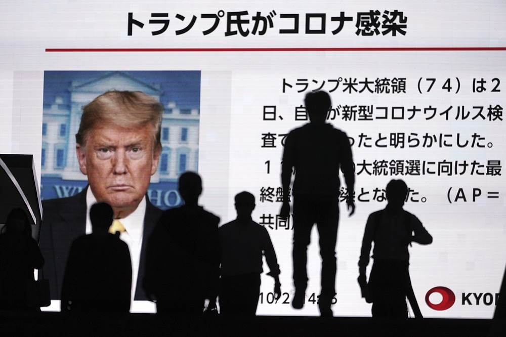 People walk past a screen showing the news report that President Donald Trump has tested positive for the coronavirus, Friday, Oct. 2, 2020, in Tokyo. President Trump said Friday that he and first lady Melania Trump have tested positive for the coronavirus, just a month before the presidential election and after having spent much of the last year largely downplaying the threat of the virus. (AP Photo/Eugene Hoshiko)
