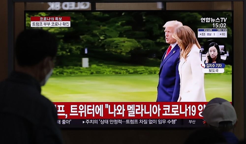 """People wearing face masks watch a TV screen reporting about U.S. President Donald Trump and first lady Melania Trump during a news program with a file footage at the Seoul Railway Station in Seoul, South Korea, Friday, Oct. 2, 2020. Trump said early Friday that he and Melania Trump have tested positive for the coronavirus, a stunning announcement that plunges the country deeper into uncertainty just a month before the presidential election. The Korean letters read: """"President Donald Trump tweeted, I and first lady Melania Trump tested positive for COVID-19."""" (AP Photo/Lee Jin-man)"""