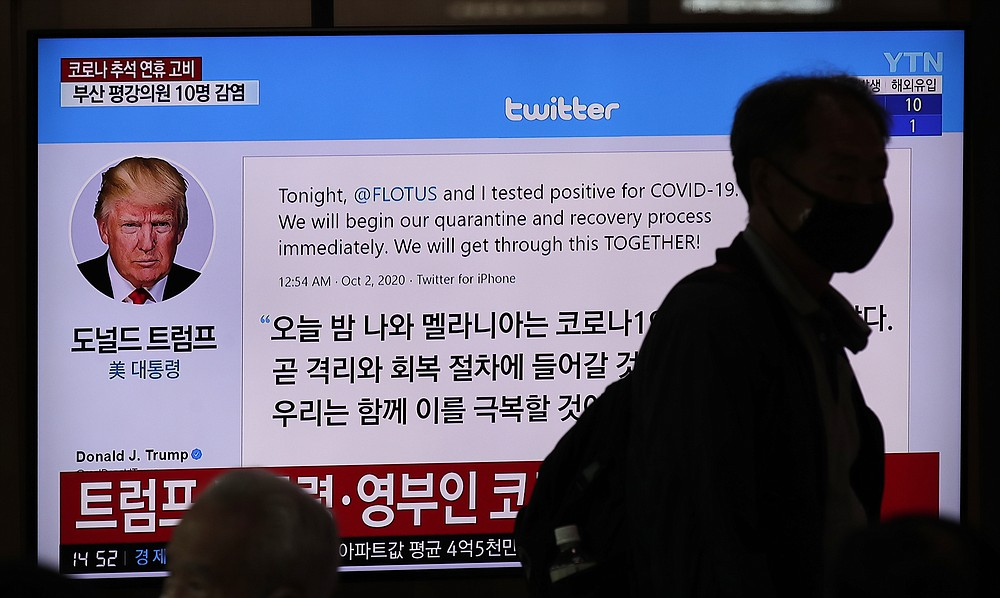 A man wearing a face mask walks near a TV screen showing an image of U.S. President Donald Trump's twitter during a news program at the Seoul Railway Station in Seoul, South Korea, Friday, Oct. 2, 2020. Trump said early Friday that he and first lady Melania Trump have tested positive for the coronavirus, a stunning announcement that plunges the country deeper into uncertainty just a month before the presidential election. (AP Photo/Lee Jin-man)