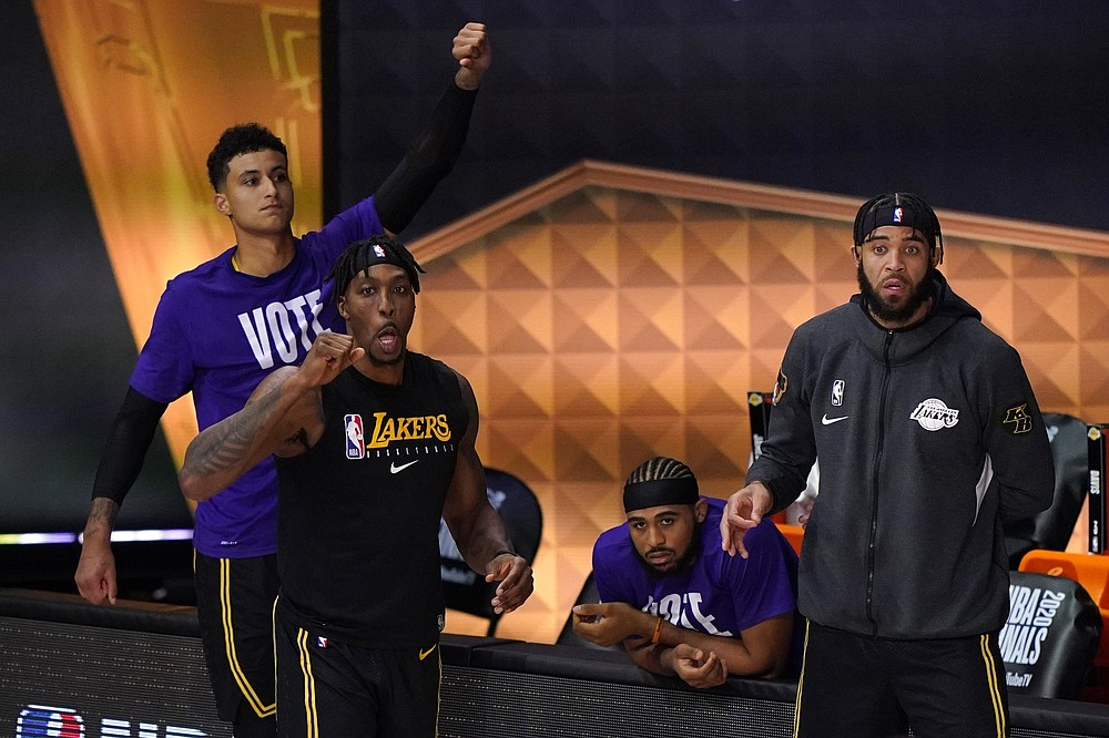 Los Angeles Lakers' Dwight Howard, left front, Kyle Kuzma, left rear, and JaVale McGee, right, celebrate in the closing seconds of Game 2 of basketball's NBA Finals against the Miami Heat on Friday, Oct. 2, 2020, in Lake Buena Vista, Fla. The Lakers won 124-114. (AP Photo/Mark J. Terrill)