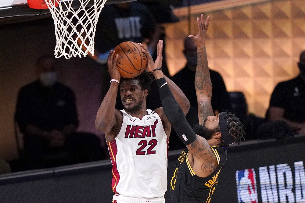 Miami Heat's Jimmy Butler (22) looks to make a pass from beneath the basket as Los Angeles Lakers' Markieff Morris, right, defends during the second half of Game 2 of basketball's NBA Finals, Friday, Oct. 2, 2020, in Lake Buena Vista, Fla. (AP Photo/Mark J. Terrill)