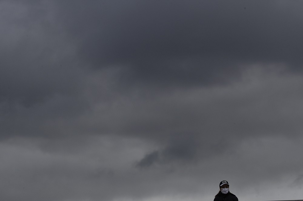 A lone spectator is silhouetted against rain clouds passing over third round matches of the French Open tennis tournament at the Roland Garros stadium in Paris, France, Saturday, Oct. 3, 2020. (AP Photo/Alessandra Tarantino)