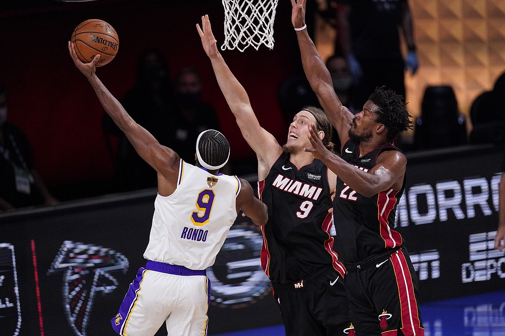 Miami Heat's Kelly Olynyk (9) and Miami Heat's Jimmy Butler (22) attempt to block Los Angeles Lakers' Rajon Rondo (9) during the second half in Game 3 of basketball's NBA Finals, Sunday, Oct. 4, 2020, in Lake Buena Vista, Fla. (AP Photo/Mark J. Terrill)
