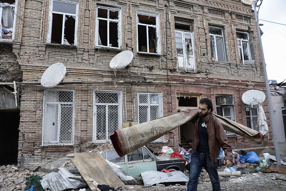 A person carries a carpet as he walks past buildings in a residential area in Ganja, Azerbaijan, damaged by shelling by Armenian forces, Monday, Oct. 5, 2020. The fighting between Armenian and Azerbaijani forces over the separatist territory of Nagorno-Karabakh resumed Monday, with both sides accusing each other of launching attacks. The region lies in Azerbaijan but has been under the control of ethnic Armenian forces backed by Armenia since the end of a separatist war in 1994. (Unal Cam/DHA via AP)