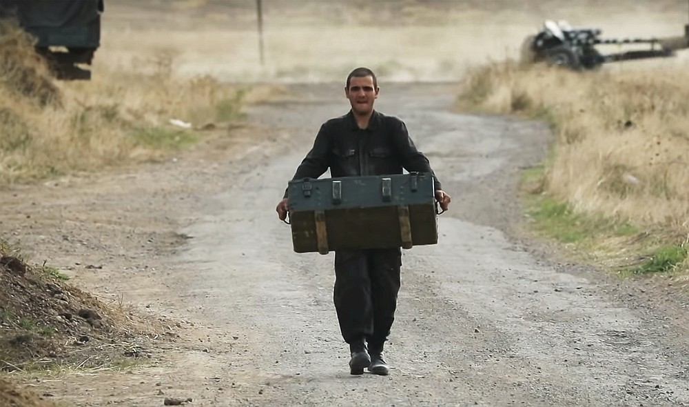 In this image taken from video released by Armenian Defense Ministry on Monday, Oct. 5, 2020, anArmenian soldier carries a box of ammunition at the contact line of the self-proclaimed Republic of Nagorno-Karabakh, Azerbaijan. Armenian military officials on Monday reported missile strikes hitting Stepanakert, the capital of Nagorno-Karabakh. The region lies in Azerbaijan but has been under the control of ethnic Armenian forces backed by Armenia since 1994. (Armenian Defense Ministry via AP)