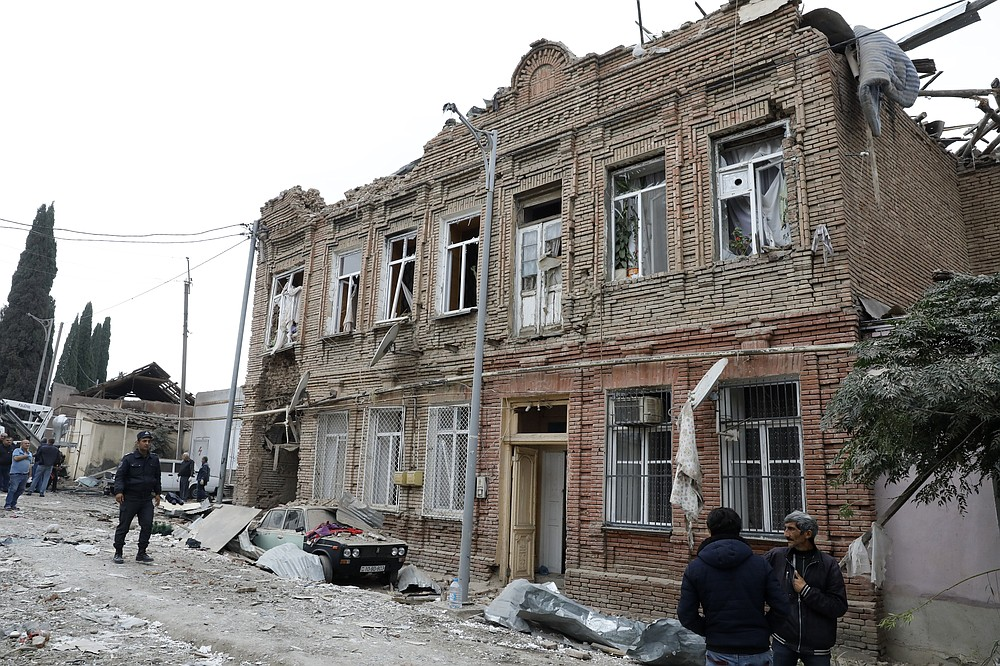 People look at a destroyed historical building in a residential area in Ganja, Azerbaijan, near the border with Armenia, after shelling by Armenian forces that killed two people and wounded several other, Sunday, Oct. 4, 2020. Turkey's foreign ministry has condemned an attack on Ganja, Azerbaijan's second largest city and said the attack was proof of Armenia's disregard for law. (DHA via AP)