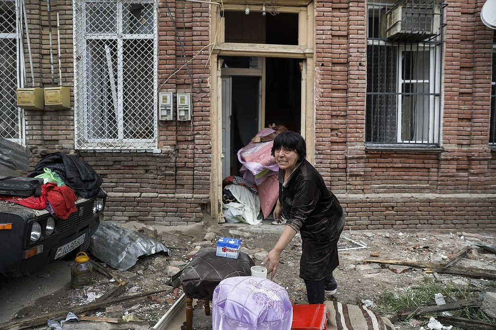 A woman, salvages belongings from a house damaged by shelling by Armenian forces, in a residential area of the city of Ganja, Azerbaijan's second-largest city, Monday, Oct. 5, 2020. The fighting between Armenian and Azerbaijani forces over the separatist territory of Nagorno-Karabakh resumed Monday, with both sides accusing each other of launching attacks. The region lies in Azerbaijan but has been under the control of ethnic Armenian forces backed by Armenia since the end of a separatist war in 1994. (Unal Cam/DHA via AP)