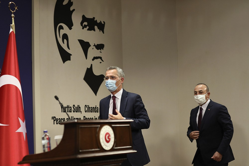 """NATO Secretary-General Jens Stoltenberg, left, and Turkey's Foreign Minister Mevlut Cavusoglu arrive for a joint press conference after their talks in Ankara, Turkey, Monday, Oct. 5, 2020. Stoltenberg said the 30-country military alliance is """"deeply concerned by the escalation of hostilities """" between Azerbaijan and Armenia and he urged Turkey to help end the fighting. (AP Photo/Burhan Ozbilici)"""