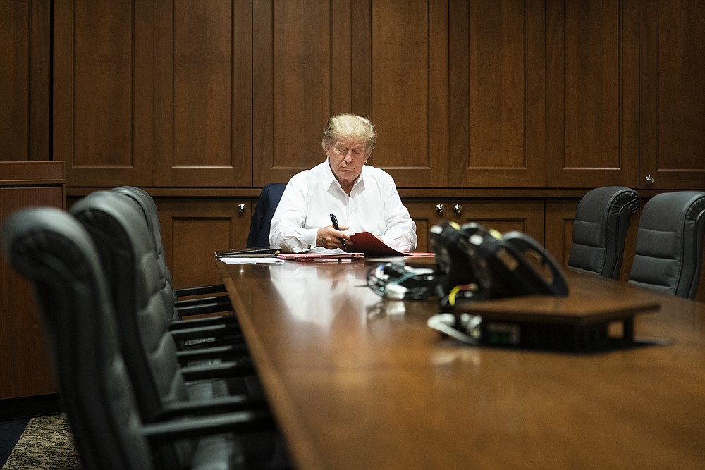 In this image released by the White House, President Donald Trump works in his conference room at Walter Reed National Military Medical Center in Bethesda, Md., Saturday, Oct. 3, 2020, after testing positive for COVID-19. (Joyce N. Boghosian/The White House via AP)