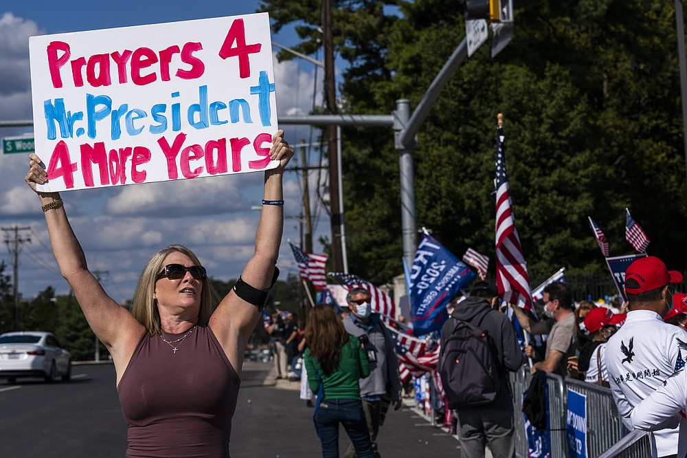 Karen Simon from the District of Columbia, let, waves a banner together with other supporters of President Donald Trump, gathered outside the Walter Reed National Military Medical Center in Bethesda, Md., Monday, Oct. 5, 2020. Trump said Monday he's leaving the military hospital where he has been treated for COVID-19 and will continue his recovery at the White House. (AP Photo/Manuel Balce Ceneta)