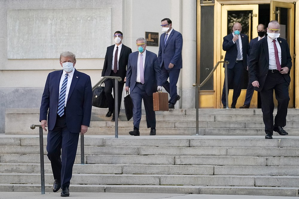 President Donald Trump, left, walks out of Walter Reed National Military Medical Center to return to the White House after receiving treatments for covid-19, Monday, Oct. 5, 2020, in Bethesda, Md. (AP Photo/Evan Vucci)