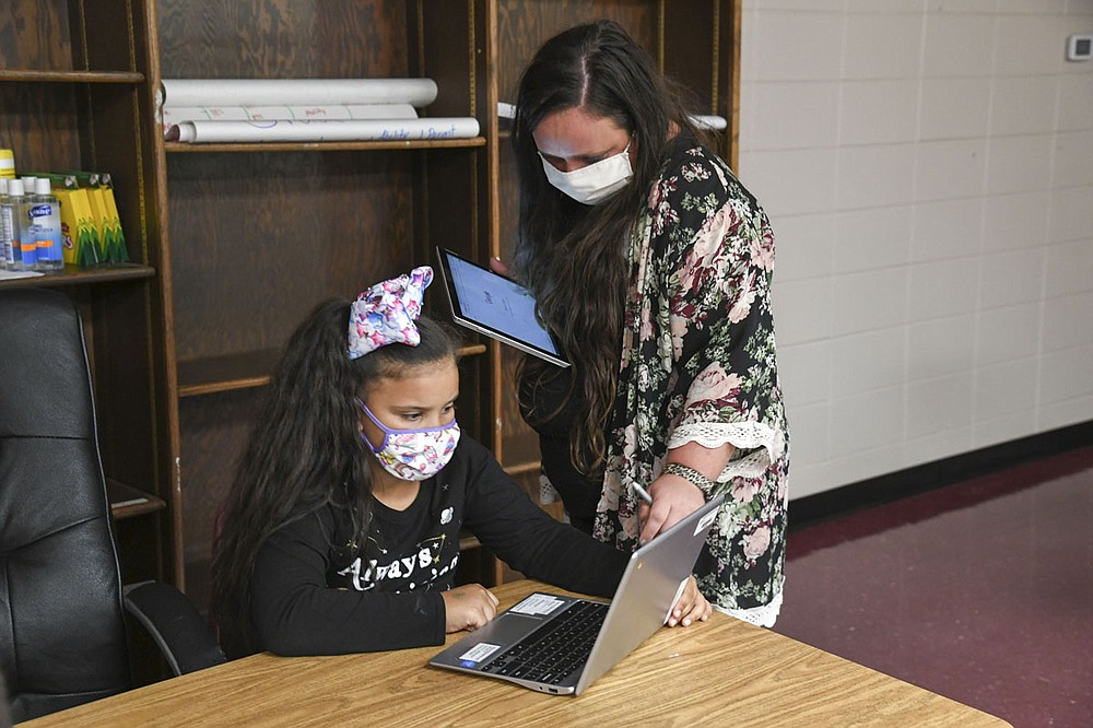 Mountain Pine's K-6 Virtual Liaison Lillian Alderman, left, helps second-grade student Jaleah Standoak log into her Chromebook on Wednesday. - Photo by Grace Brown of The Sentinel-Record
