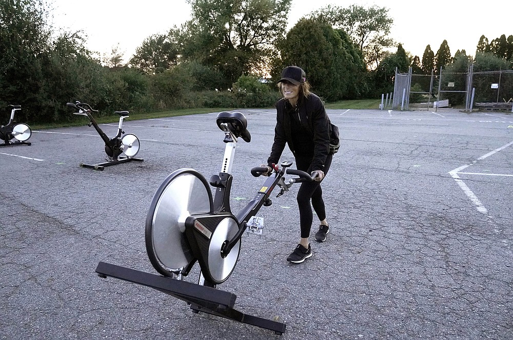 Jeanne Carter, co-owner of Fuel Training Studio, in Newburyport, Mass., removes stationary exercise bikes from a parking lot outside the gym following a spinning class, Monday, Sept. 21, 2020, in Newburyport. The gym's revenue is down about 60% during the COVID-19 pandemic. Fuel Training Studio plans to continue holding outdoor classes into the winter with the help of a planned greenhouse-like structure with heaters but no walls. (AP Photo/Steven Senne)