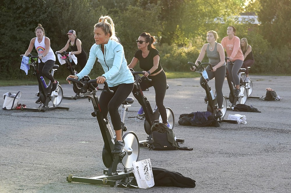 Jackie Brennan, of Merrimac, Mass., front, pedals on a stationary exercise bike with others during a spinning class in a parking lot outside Fuel Training Studio, Monday, Sept. 21, 2020, in Newburyport. The gym's revenue is down about 60% during the COVID-19 pandemic. Fuel Training Studio plans to continue holding outdoor classes into the winter with the help of a planned greenhouse-like structure with heaters but no walls. (AP Photo/Steven Senne)