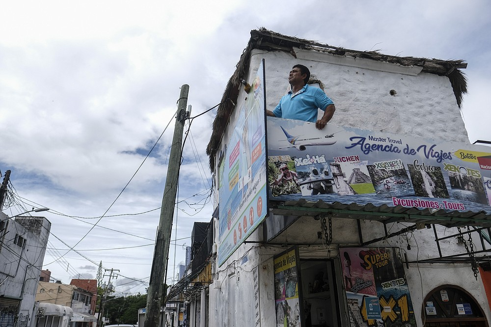 A man removes signs as Hurricane Delta approaches Puerto Juarez, Cancun, Mexico, Tuesday, Oct. 6, 2020. Hurricane Delta rapidly intensified into a potentially catastrophic Category 4 hurricane Tuesday on a course to hammer southeastern Mexico and then continue on to the U.S. Gulf coast this week. (AP Photo/Victor Ruiz Garcia)