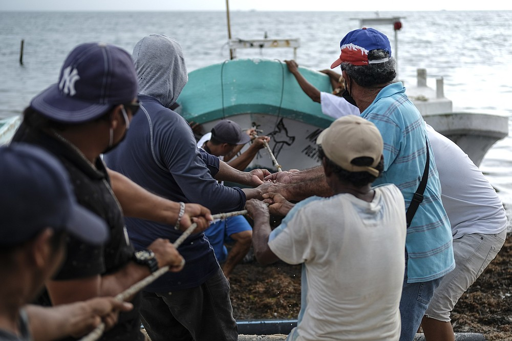 Fishermen pull in a boat before the arrival of Hurricane Delta in Puerto Juarez, Cancun, Mexico, Tuesday, Oct. 6, 2020. Hurricane Delta rapidly intensified into a potentially catastrophic Category 4 hurricane Tuesday on a course to hammer southeastern Mexico and then continue on to the U.S. Gulf coast this week. (AP Photo/Victor Ruiz Garcia)