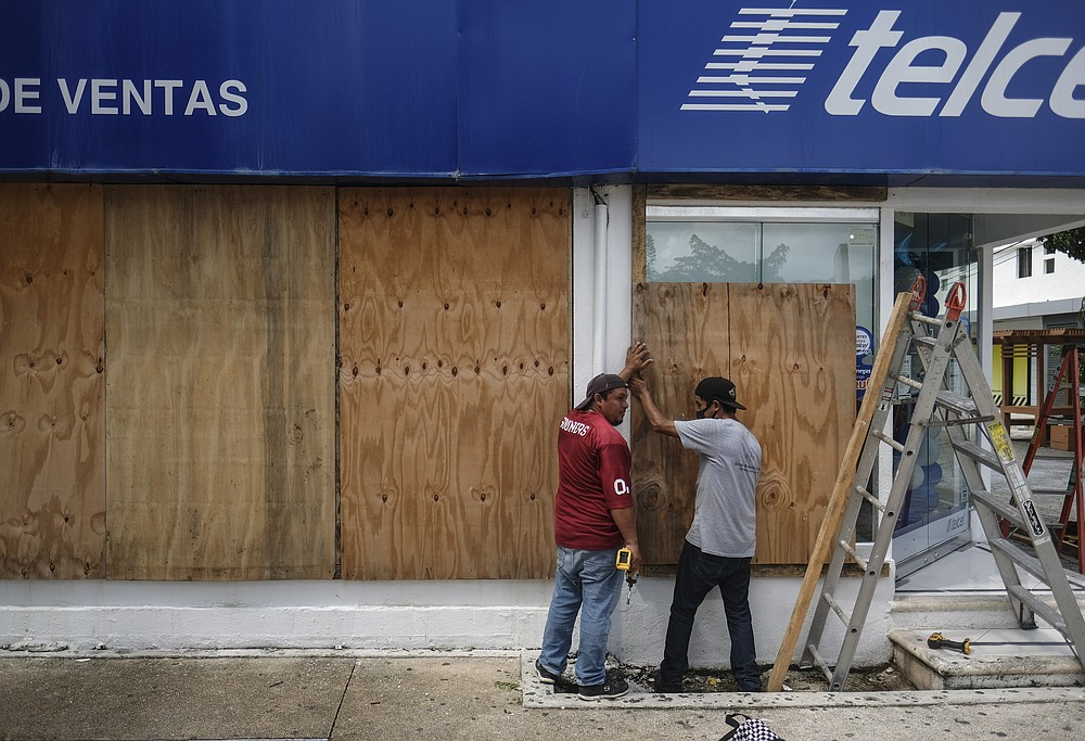 Men board up a Telcel phone store as Hurricane Delta approaches Puerto Juarez, Cancun, Mexico, Tuesday, Oct. 6, 2020. Hurricane Delta rapidly intensified into a potentially catastrophic Category 4 hurricane Tuesday on a course to hammer southeastern Mexico and then continue on to the U.S. Gulf coast this week. (AP Photo/Victor Ruiz Garcia)