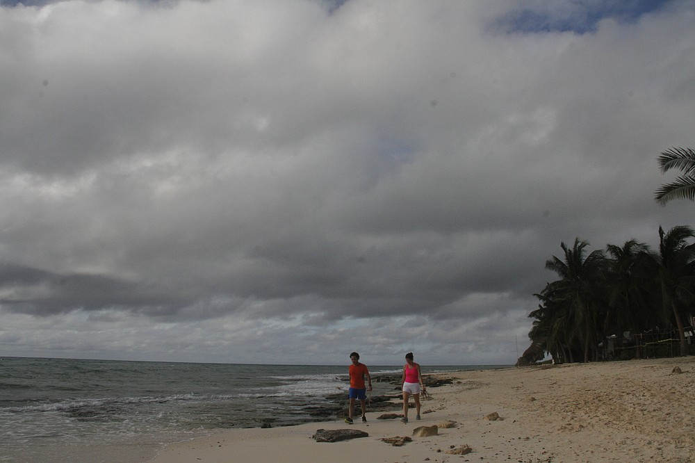 A couple walks on the beach before Hurricane Delta arrives near Playa del Carmen, Mexico, early Tuesday, Oct. 6, 2020. Hurricane Delta rapidly intensified into a Category 2 hurricane Tuesday on a course to hammer southeastern Mexico and then grow to a potentially catastrophic Category 4 on approach to the U.S. Gulf Coast this week. (AP Photo/Tomas Stargardter)