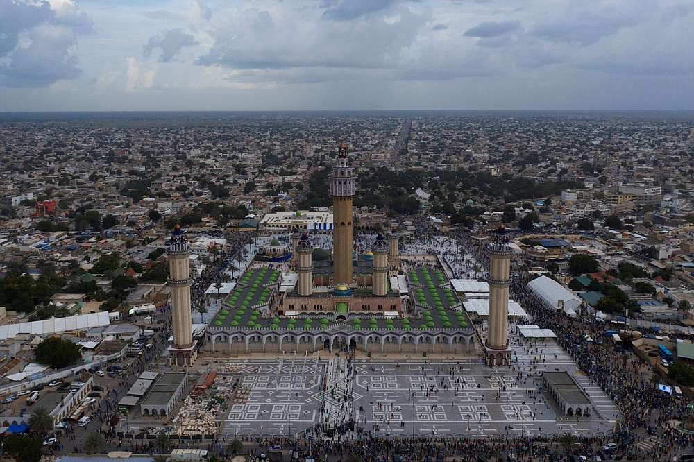 In this aerial photo taken with a drone people arrive at the Grand Mosque of Touba as they take part in the celebrations of the Grand Magal of Touba, Senegal, Monday, Oct. 5, 2020. Despite the coronavirus pandemic, thousands of people from the Mouride Brotherhood, an order of Sufi Islam, are gathering for the annual religious pilgrimage to celebrate the life and teachings of Cheikh Amadou Bamba, the founder of the brotherhood. (AP Photo/Leo Correa)