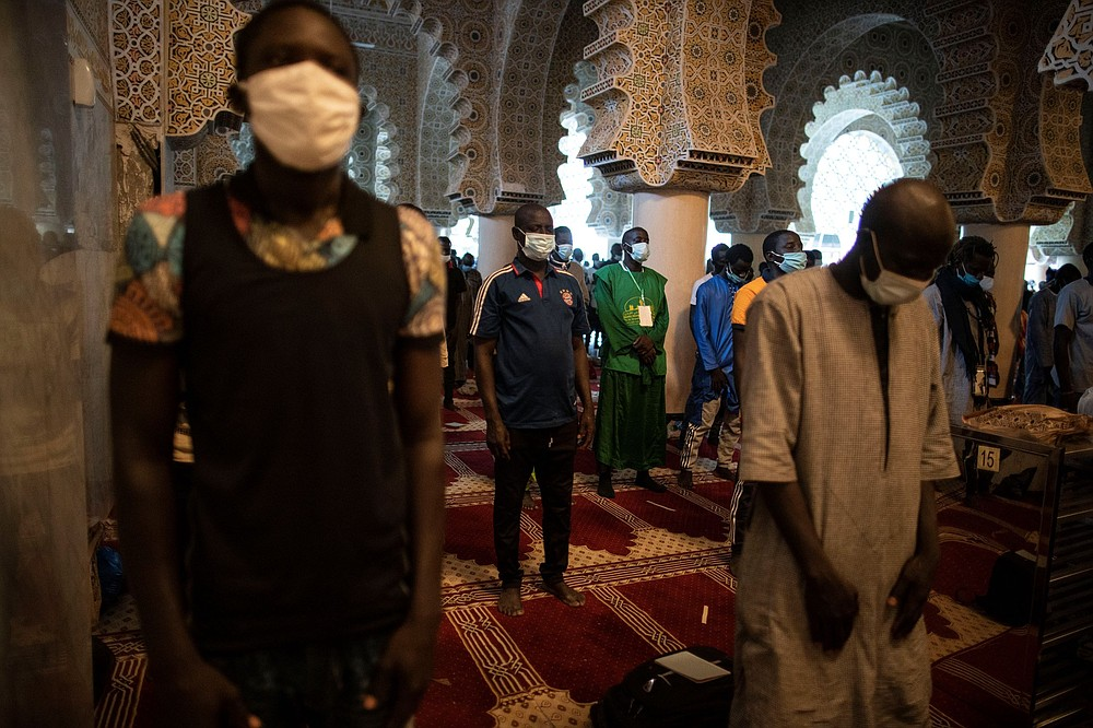 Wearing protective masks, pilgrims from the Mouride Brotherhood, pray in the Grand Mosque of Touba as they take part in the celebrations of the Grand Magal of Touba, Senegal, Monday, Oct. 5, 2020. Despite the coronavirus pandemic, thousands of people from the Mouride Brotherhood, an order of Sufi Islam, are gathering for the annual religious pilgrimage to celebrate the life and teachings of Cheikh Amadou Bamba, the founder of the brotherhood. (AP Photo/Leo Correa)